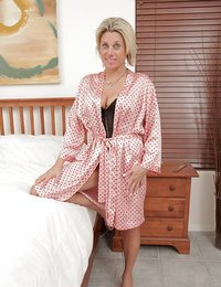 Milf relaxes in bed with..
